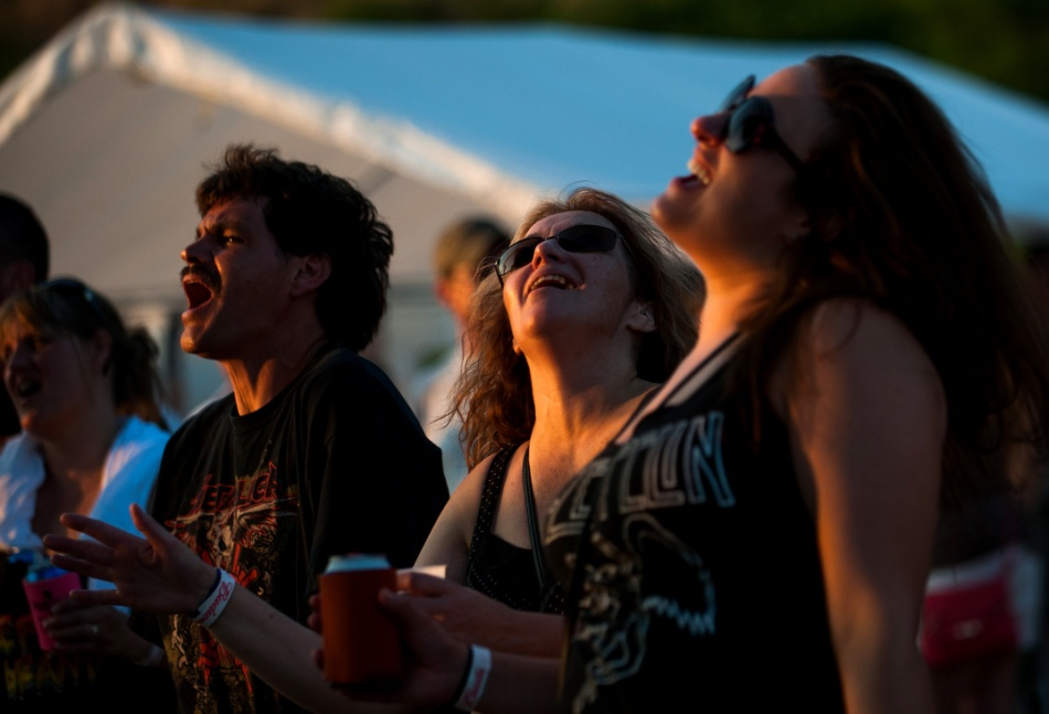 From left, Al Potter, 45, of Muskegon, Marjorie Samlow, 46, of Fruitport, and Amy Van Hees, 29, also of Fruitport, listen to the band Eighth and Amsterdam  before Pinckney resident John Fletcher, 51, performs for the last time as Ghengis John the Human Firecracker during the Conestoga Bike Fest in Coopersville, Michigan on Saturday, June 28th. Fletcher's firecracker suit had more than 10,500 firecrackers and he was hoping to set a Guinness World Record for most firecrackers ever ignited while strapped to a person's body.